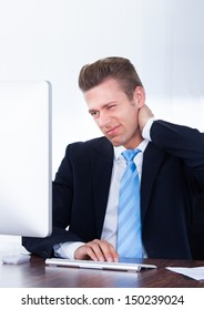 Businessman Using Computer Suffering From Neck Ache