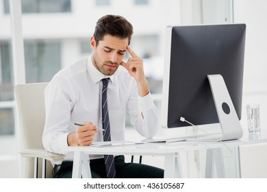 Businessman using computer and taking notes in office