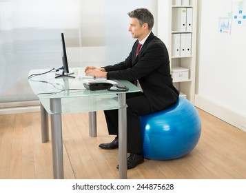 Businessman Using Computer While Sitting On Pilates Ball In Office