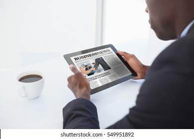 Businessman using digital tablet against business newspaper