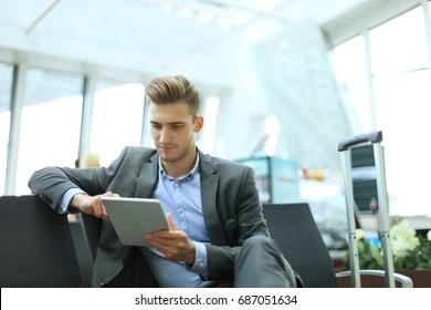 Businessman using digital tablet in airport departure lounge.