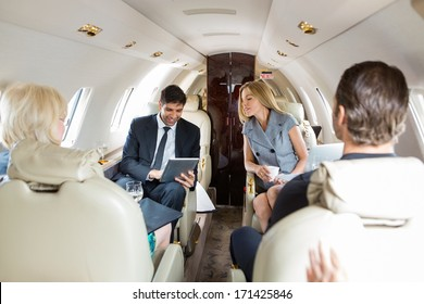 Businessman using digital tablet with colleagues in private jet