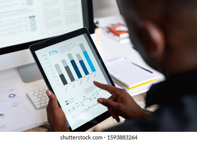 Businessman using digital tablet computer with financial data on screen in office