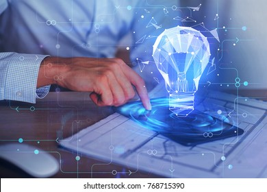 Businessman using digital tablet with glowing blue polygonal lamp projection at blurry workplace. Success and network concept. Double exposure