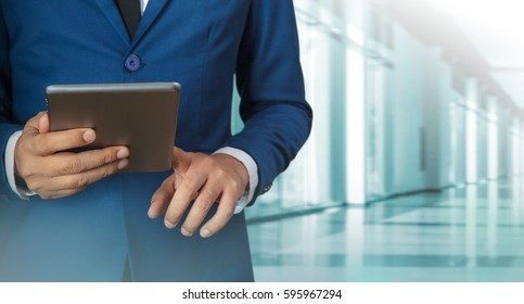 Businessman using digital tablet with modern building and social media