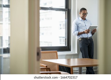 A businessman using a digital tablet, standing by a window.