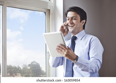 Businessman using digital tablet and talking on a cell phone