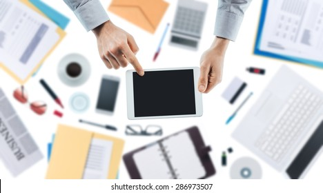 Businessman using a digital touch screen tablet, hands close up top view, desktop on background