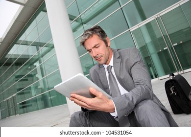 Businessman using electronic tablet in front of offices building