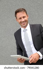 Businessman using electronic tablet leans against wall