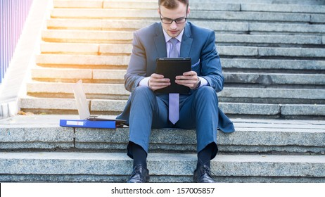 Businessman using electronic tablet pc. He is sitting on a stairs.