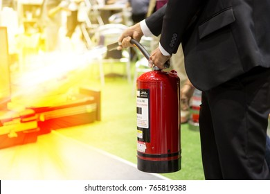 Businessman using fire extinguisher to fighting fire in the industrial factory