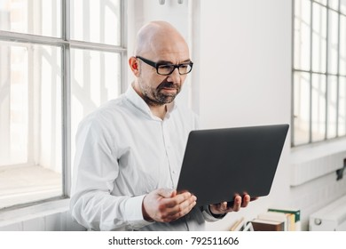 Businessman using a handheld laptop as he stands in front of a bright window reading information on the screen