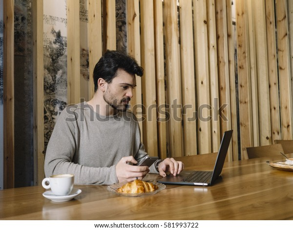Businessman using his laptop in the Coffee Shop.