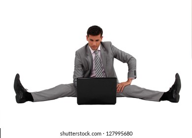 Businessman using his laptop with his legs spread apart