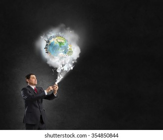 Businessman using his smartphone and Earth planet out of screen. Elements of this image are furnished by NASA
