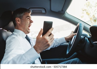 Businessman using his smartphone while driving and having a car accident, he is shocked and screaming