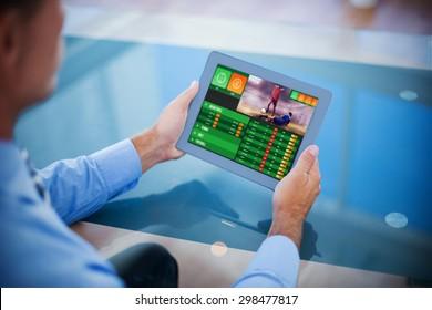 Businessman using his tablet against gambling app screen