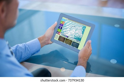 Businessman using his tablet  against composite image of various video and computer icons
