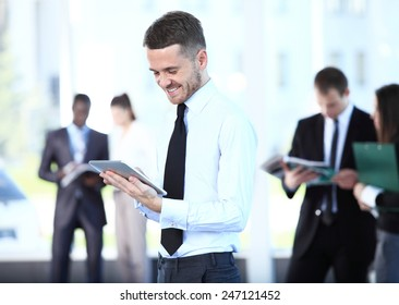Businessman using his tablet in the office. Business man working with a digital tablet