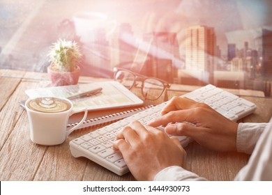 Businessman using keyboard with tablet  on wooden table  with a cup of coffee