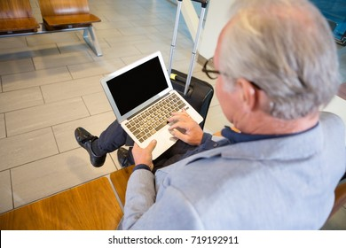 Businessman Using Laptop In Airport Waiting Area