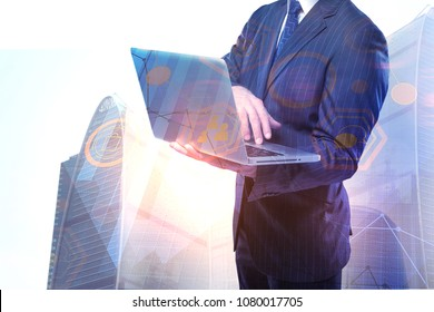 Businessman using laptop with blurry interface in city. Technology and analytics concept. Double exposure