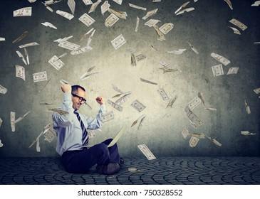 Businessman using a laptop building online business earning money under dollar bills cash rain falling down. Beginner IT entrepreneur success economy concept