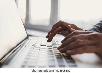 Businessman using laptop computer. Close up of male hands typing on laptop keyboard. Business working concept. Blogger, journalist writing new article