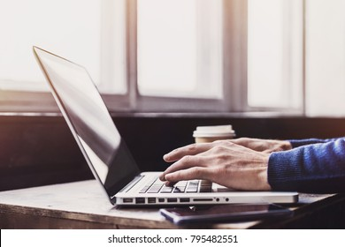 Businessman using laptop computer. Male hand typing on laptop keyboard
