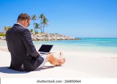 Businessman using laptop computer on tropical beach