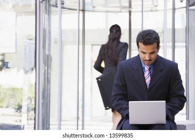 Businessman using laptop computer outside office