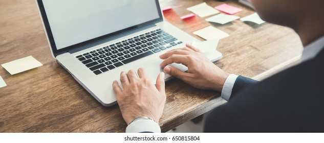 Businessman using laptop computer at working table - panoramic web banner