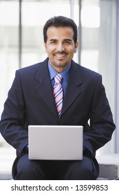 Businessman using laptop coomputer outside office