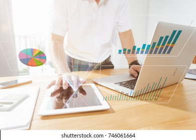 Businessman using laptop and digital tablet to analyse sales report , virtual screen show report chart from digital tablet .