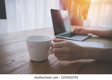 businessman using laptop and drinking some coffee in morning at home.