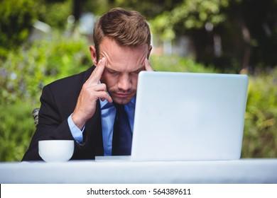Businessman using laptop having a headache in a restaurant