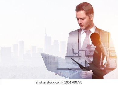 Businessman using laptop and holding contract on abstract office and city background with copy space. Finance and technology concept. Double exposure