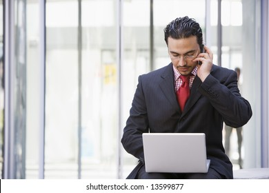 Businessman using laptop and mobile outside office