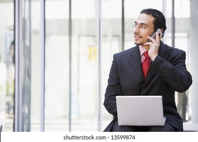 Businessman using laptop and mobile phone outside office