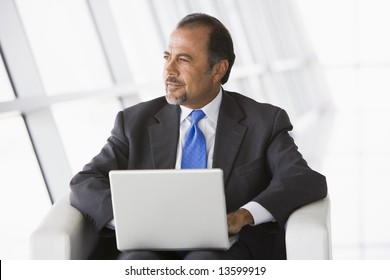 Businessman using laptop in office lobby