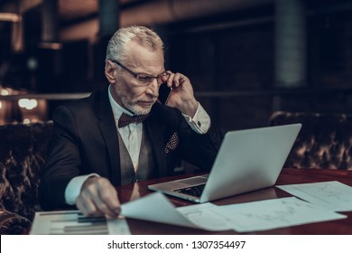 Businessman Using Laptop. Old Businessman talking on Phone . Man is Wearing in Black Suit. Experienced Entrepreneur. Strict Man. looking at Laptop. holding piece of paper.  man with glasses