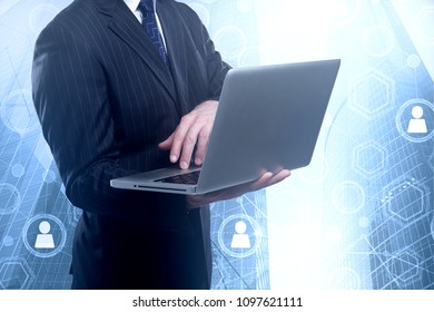 Businessman using laptop on abstract blurry city background with business interface. Technology, media and analytics concept. Double exposure