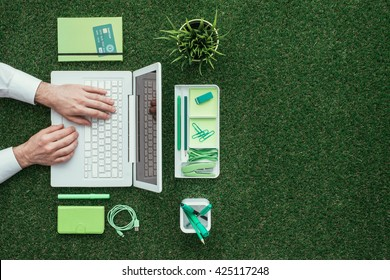 Businessman using a laptop on the grass outdoors; green business and technology concept, top view