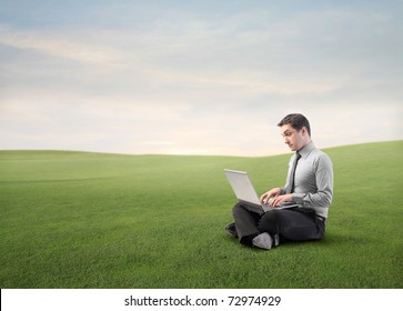 Businessman using a laptop on a green meadow