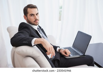 Businessman using laptop on his couch at home in the living room. Working from home in quarantine lockdown. Social distancing Self Isolation