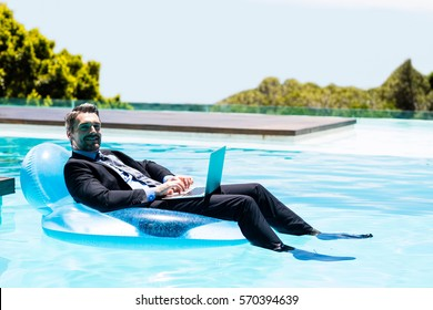 Businessman using laptop on inflatable in swimming pool