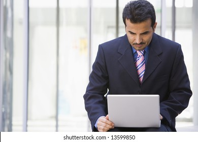 Businessman using laptop outside office