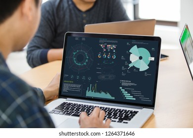 Businessman using laptop with project statistics data, analyzing financial graphs and charts showing company growth on screen at meeting.