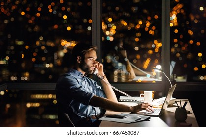 Businessman using a laptop and talking on the phone at his office desk late into the night in front of windows overlooking the city
